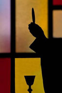 Silhouette of a Priest Lifting Host During Catholic Mass Journal